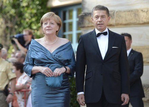 Angela Merkel und ihr Ehemann Joachim Sauer: Die Bundeskanzlerin trug dasselbe Kleid bereits im Jahr 2008. Fotos: epa; dapd
