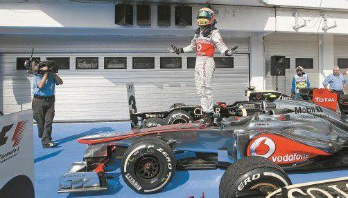 Der Engländer Lewis Hamilton posierte nach seinem souveränen Sieg beim Grand Prix von Ungarn triumphierend auf seinem McLaren. Foto: Reuters