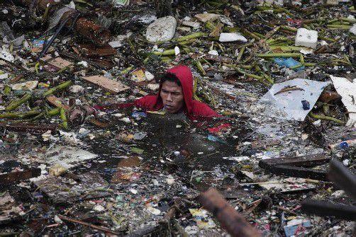 Nur mühsam kann sich dieser Anwohner durchs Wasser bewegen, um die Überreste seines Besitzes zu bergen. Foto: REUTERS