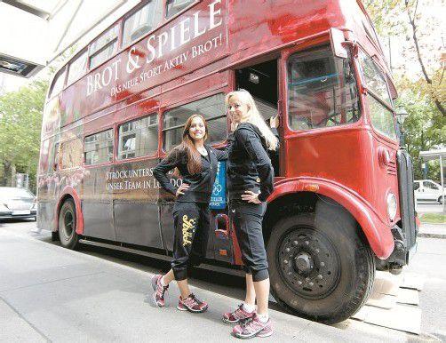 """Österreichs Synchron-""""Nixen"""" Livia Lang und Nadine Brandl nehmen Aufstellung vor einem der berühmten britischen Doppeldeckerbusse. Foto: APA"""