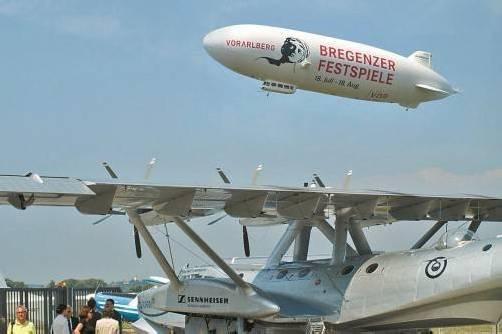 Aller guten Dinge sind drei: Der Zeppelin mit seiner Festspiel-Werbung über der legendären DO 24 bei ihrem Kurzbesuch am Bodensee.  Foto: stp