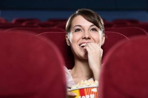 Young woman with popcorn watching a movie