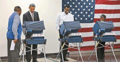 Der US-Präsident ist nur der erste unter gleichen Bürgern: Barack Obama (2. v. l.) gab in diesem Sinne in einem Wahllokal in Chicago vorab seine Stimme ab. Der reguläre Wahltag ist erst am 6. November. Foto: Reuters