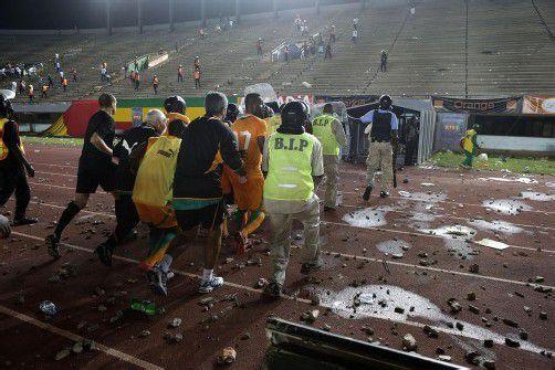 Die Spieler, im Bild Akteure der Elfenbeinküste, und das Schiedsrichtergespann mussten unter Polizeischutz in Sicherheit gebracht werden. Foto: ap