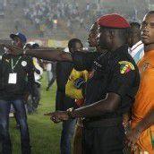 Ein Polizist aus Senegal stellt sich schützend vor Didier Drogba.