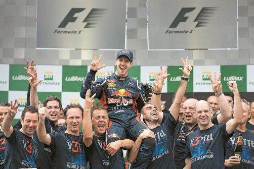 Aller guten Dinge sind drei: Das Team von Red Bull Racing lässt Sebastian Vettel nach dem Gewinn des WM-Titels hochleben. Foto: reuters
