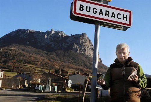 """Bürgermeister Jean-Pierre Delord vor dem Ortsschild des Dorfes im Süden Frankreichs: """"Wir sind zur Attraktion geworden."""" Foto: DPA"""