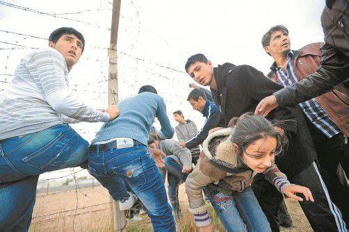Vor den Kämpfen zwischen Assad-Truppen und Rebellen retteten sich gestern viele Syrer durch einen Stacheldrahtzaun in die Türkei. Foto: EPA