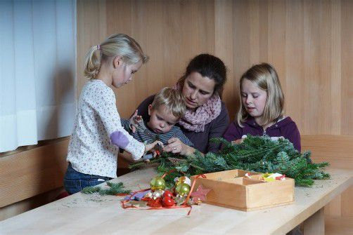 He, das zwickt aber! Der zweijährige Josef und seine Schwestern Pia (7) und Anna (10) haben den Adventkranz gemeinsam mit ihrer Mutter Sigrid gebunden. Die vier sind ein eingespieltes Team. Fotos: l. Berchtold