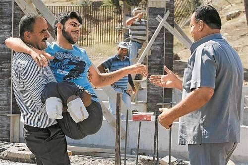 Der verletzte 23-jährige Mustafa Abu Bekir reagierte gestern erleichtert, als er einem seiner Verwandten begegnete, nachdem er es von Syrien in die Türkei geschafft hatte. Foto: AP