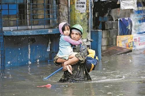 Dieser Mann trägt seine Tochter östlich von Manila durch die überschwemmten Straßen. Fotos: EPA