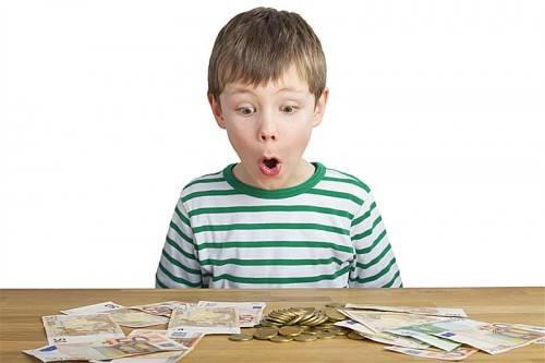 Junge sitzt staunend vor Geldmünzen und Scheinen