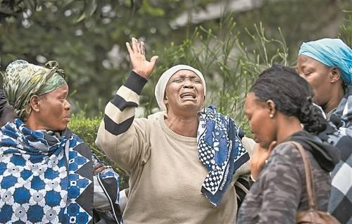 """Schock in Kenia: Mary Italo (Mitte) trauert um ihren 33-jährigen Sohn Thomas Abaya, der bei dem Geiseldrama im Einkaufszentrum """"Westgatemall"""" in Nairobi getötet wurde. Foto: AP"""