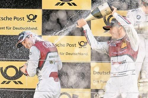 Timo Scheider (r.) verpasst dem DTM-Meister Mike Rockenfeller eine Champagnerdusche. Foto: audi