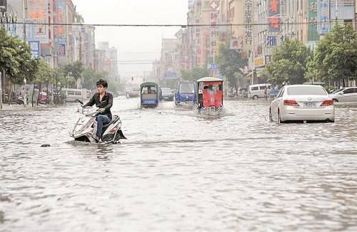 Was muss, das muss: Einige Verkehrsteilnehmer bahnen sich trotz Wassermassen ihren Weg durch die chinesische Stadt Shanwei. Foto: Reuters