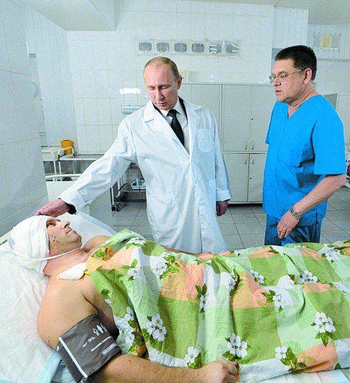 Putin (Bildmitte) am Bett eines Verletzten. Foto: EPA