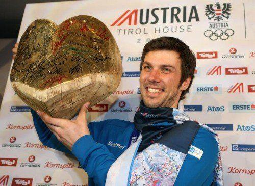 Goldmedaillengewinner Mario Matt posiert bei der Party im Austria Tirol Haus mit dem Gold-Herz aus Holz. Foto: gepa