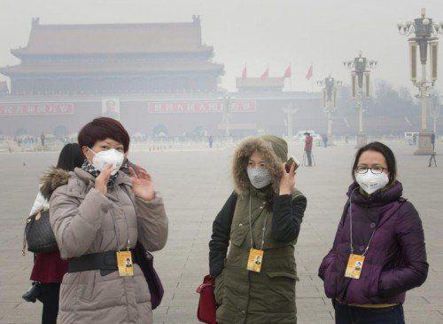 Viele Menschen, so auch diese Journalistinnen, versuchen sich mit Atemschutzmasken gegen die rauchige, dreckige Luft zu schützen.  Foto: EPA