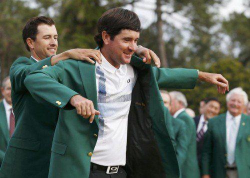 Der geschlagene Titelverteidiger Adam Scott (hinten) hilft US-Open-Gewinner Bubba Watson in das grüne Sieger-Jackett. Fotos: ap/2