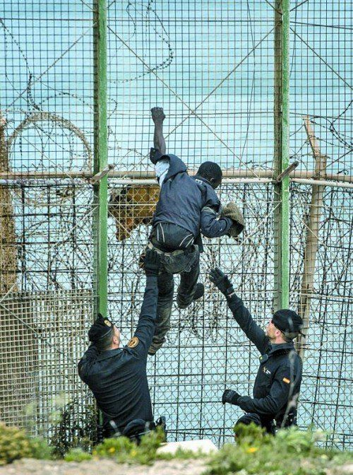 Zurück nach Afrika: Flüchtling mit spanischen Beamten. Foto: AP