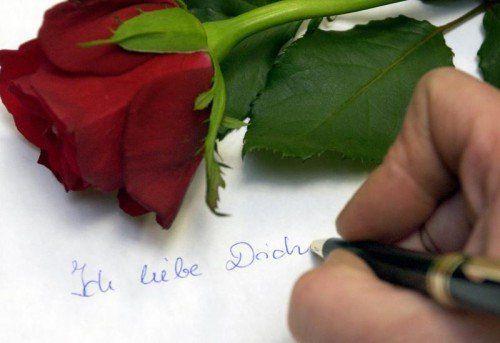 ARCHIV - Ein Mann schreibt am 10.02.2004 in Frankfurt (Oder) auf eine Blatt Papier auf dem eine rote Rose liegt «Ich liebe Dich». Valentinstag ist Hoch-Zeit für Liebesschwüre. Doch die werden inzwischen oft per SMS oder E-Mail verschickt statt als klassischer Liebesbrief. Foto: Patrick Pleul/dpa (zu dpa-Interview lth «Expertin: Klassischer Liebesbrief kommt zum Valentinstag gut an» vom 08.02.2013) +++(c) dpa - Bildfunk+++