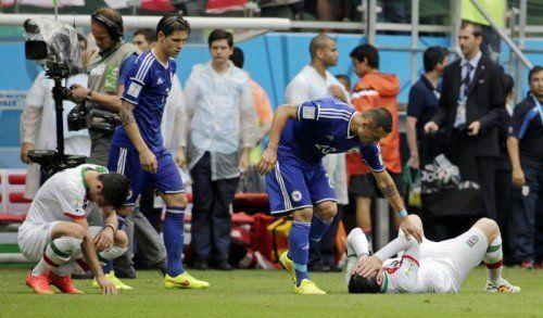 Die Bosnier trösteten nach ihrem ersten WM-Sieg die Gegner. Sie hatten nämlich die Achtelfinal-Träume der Iraner zerplatzen lassen. Foto: ap