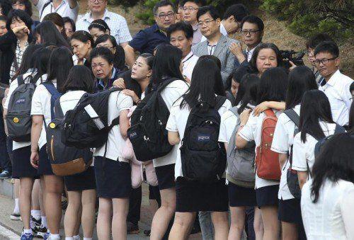Für die Überlebenden beginnt wieder der Alltag. Vor der Schule verabschiedeten sich die Jugendlichen von ihren Eltern. Foto: AP