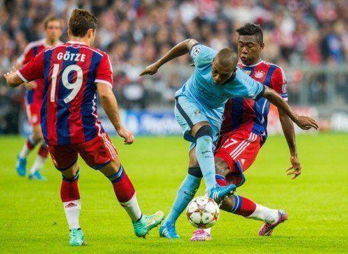 Die Münchner David Alaba (rechts) und Mario Götze (links) mit dem Versuch, den Brasilianer im Team von Manchester City, Fernandinho, zu stoppen. Foto: epa