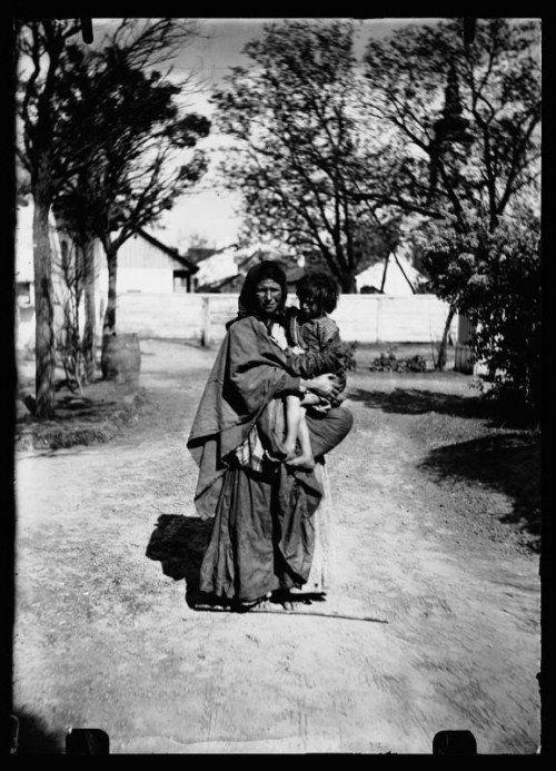 Frau mit Kind am Arm auf einer Straße in Ungarn. Wahrscheinlich Roma.