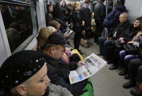 In der U-Bahn in Kiew entnehmen Bürger am Tag nach der Wahl die Ergebnisse der Parlamentswahl aus der Tageszeitung. foto: AP