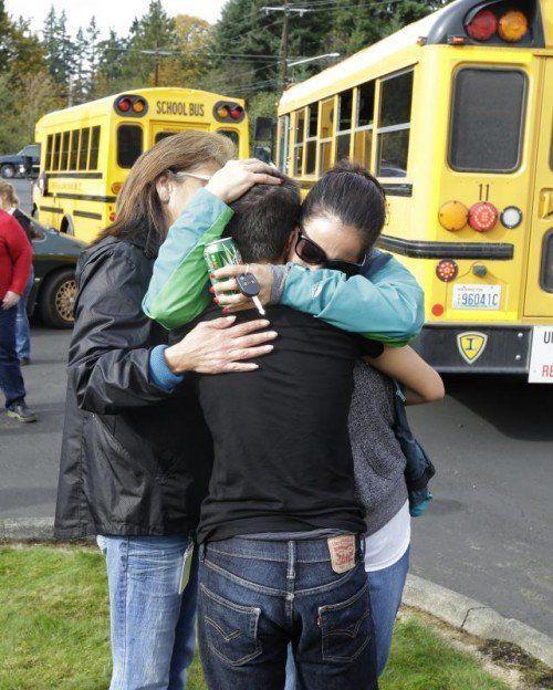 Menschen umarmen sich vor der High School in Marysville. Foto: AP