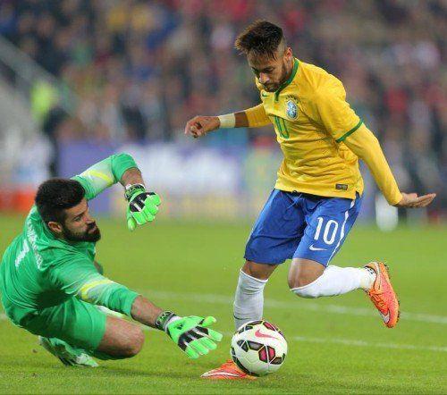 Brazil's Neymar JR, right, is about to pass Turkey's goalkeeper Volkan Demirel to score a goal during their friendly soccer match with Turkey at Sukru Saracoglu Stadium in Istanbul, Turkey, Wednesday, Nov. 12, 2014. (AP Photo)