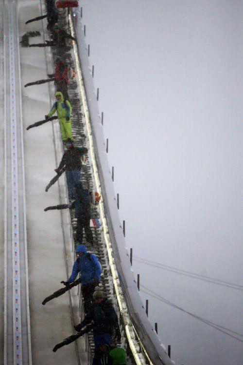Viele Helfer waren stundenlang im Einsatz. Trotz großer Bemühungen musste der Eröffnungsbewerb in Oberstdorf abgesagt werden. Foto: epa