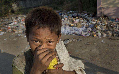 Auf der Suche nach Nahrung wühlen sich die Kinder durch Berge von Ab-fall. Um Hunger zu betäuben, schnüffeln viele von ihnen Klebstoff. AP