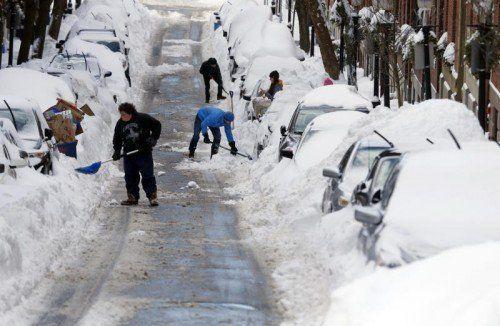 Autos freischaufeln, was das Zeug hält: Der Wintersturm traf Boston mit voller Wucht.  Foto: AP