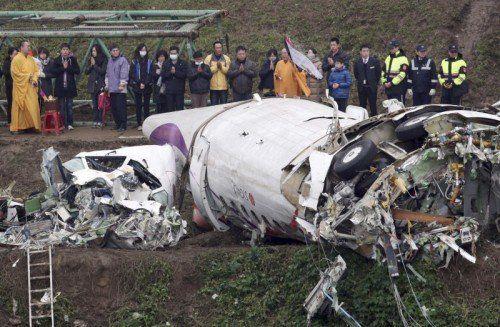 Angehörige der Opfer beten neben dem Wrack des abgestürzten Flugzeugs. Sie kamen in Begleitung buddhistischer Mönche. Foto: AP