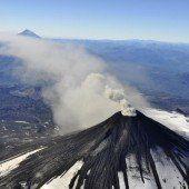Vulkan spuckt Rauch und Asche