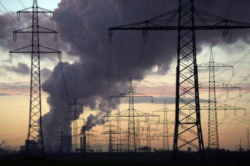 Strommasten sind am 13.01.2014 bei Sonnenuntergang auf einem Feld bei Pulheim (Nordrhein-Westfalen) zu sehen. Dahinter stehen die Kühltürme des RWE-Kraftwerks Niederaußem. Foto: Federico Gambarini/dpa +++(c) dpa - Bildfunk+++
