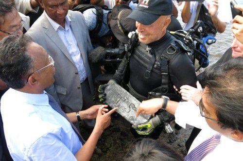 Barry Clifford überreichte den rund 50 Kilo schweren Silberbarren an Präsident Hery Rajaonarimampianina.  Foto: AP