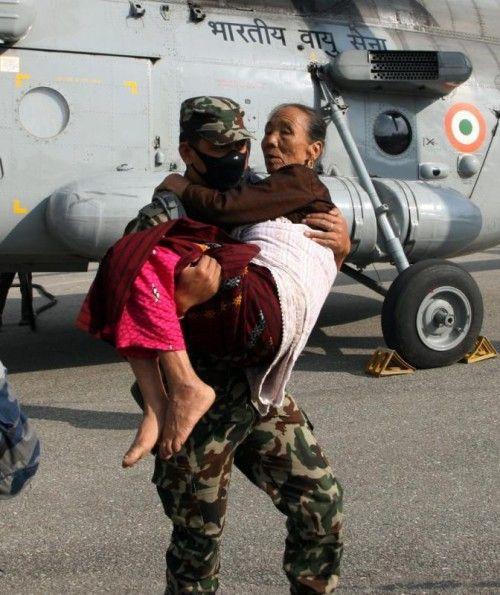 Ein nepalesischer Offizier trägt eine hilflose Frau in einen Rettungshubschrauber. Foto: EPA