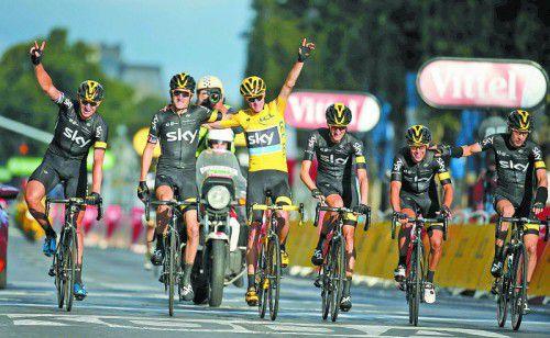 Tour-de-France-Triumphator Christopher Froome wird von den Kollegen des Sky-Teams in Paris ins Ziel geleitet.