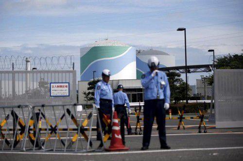 Sicherheitsbeamte bewachen das AKW Sendai. Zahlreiche Menschen protestierten gegen die Wiederinbetriebnahme.