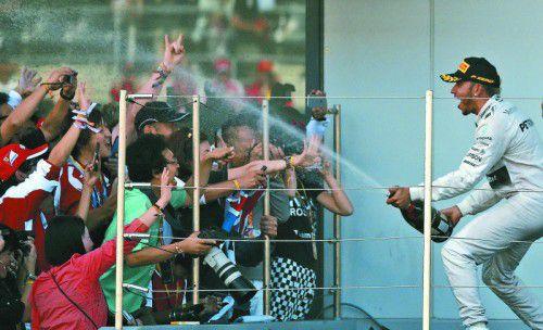 Champagner für die japanischen Fans: Lewis Hamilton feiert in Suzuka ausgelassen seinen achten Saisonsieg.