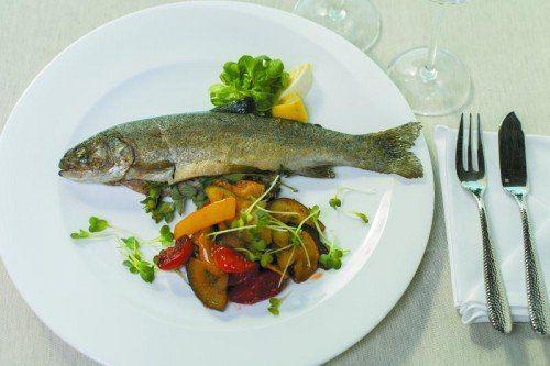 Frische Forelle auf einem Bett von mediterranem Gemüse und frischen Kräutern.