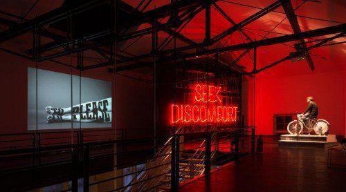 """Stefan Sagmeisters """"Happy Show"""" im MAK: ein Fahrrad treibt unter anderem die Neon-Leuchtschrift """"Seek Comfort"""" an."""