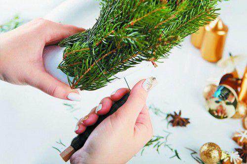 Fixieren Sie die Zweige in kleinen Büscheln fest mit einem Draht rund um den Kranz.