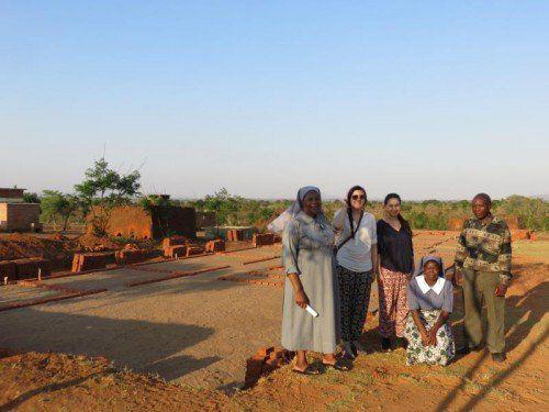 Anna Pirker und Julia Schweiger mit ihren Gastgebern vor dem Rohbau der Geburtenstation.
