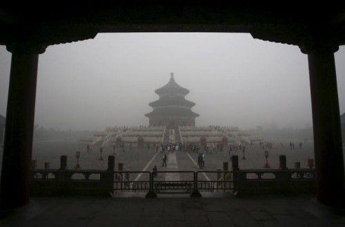 Menschen besuchen den Himmelstempel in Peking, während eine graue Smog-Wolke auf der 22-Millionen-Metropole liegt.