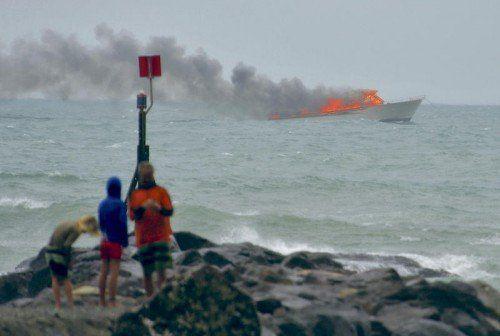Menschen beobachten von der Küste aus das brennende Touristenboot. Alle Passagiere konnten sich retten.