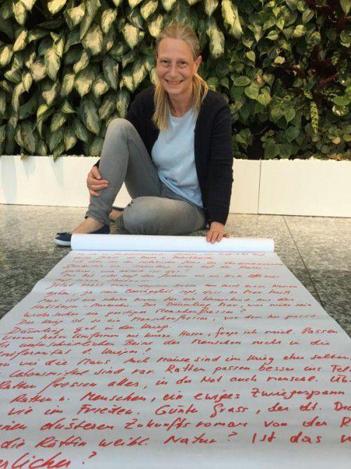 """Tamara Ofner mit einer Papierrolle, auf der die Ergebnisse einer """"Free Writing""""-Übung zu lesen sind."""